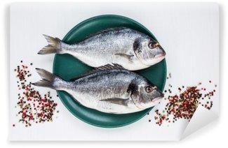 Fototapet av Vinyl Rå dorado fisk på gul skylt med pepparkorn på vitt bord. Ovanifrån, textutrymme