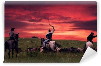 Fototapet av Vinyl Tre cowboys kör flock hästar på en solnedgång