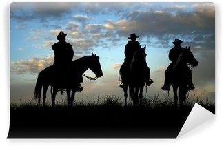 Fototapet av Vinyl Tre cowboys till häst silhuett mot gryningen sky