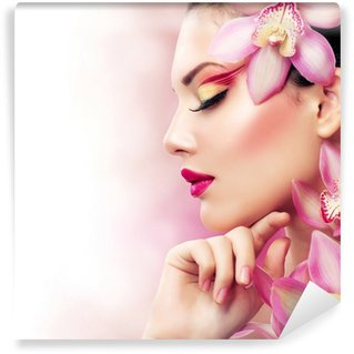 Fototapet av Vinyl Vacker flicka med Orchid blommor. Perfect Make-up