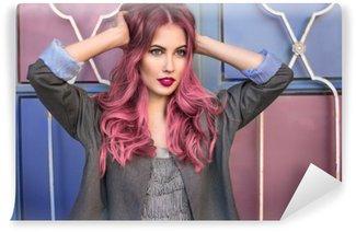Fototapet av Vinyl Vacker hipster modell med lockigt rosa hår poserar framför den färgstarka väggen