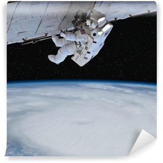 Vinylová Fototapeta Astronaut pracuje na oběžné dráze nad Zemí. Hvězdy v pozadí.