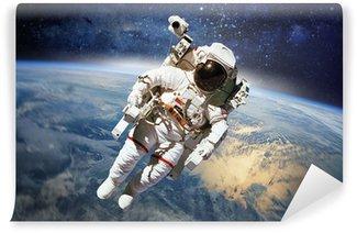 Vinylová Fototapeta Astronaut ve vesmíru s planetě Zemi jako pozadí. Prvky