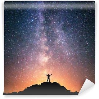 Vinylová Fototapeta Člověk a vesmír. Osoba, která stojí na vrcholu kopce vedle Galaxie s rukama zvedl do vzduchu.