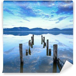 Fototapeta Winylowa Drewniane molo i pomost pozostaje na jeziorze o zachodzie słońca. Toskania, Włochy