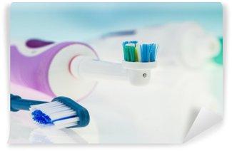 Fototapeta Vinylowa Elektryczna szczoteczka do zębów i klasyczny na powierzchni odbijającej i jasnoniebieskim tle.