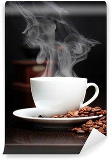 Fototapeta Winylowa Filiżanka kawy z dymu, szlifierki i ziarna na czarnej ścianie.