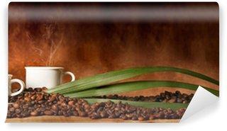 Fototapeta Vinylowa Filiżanka kawy z ziaren kawy rozrzucone na stole