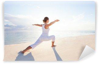 Fototapeta Vinylowa Kaukaski kobieta uprawiania jogi na brzegu morza