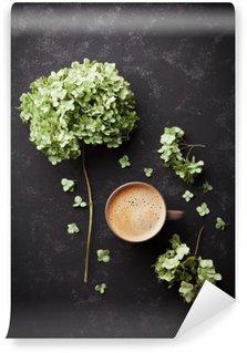 Fototapeta Winylowa Kompozycja z filiżanką kawy i suszonych kwiatów hortensji na czarnym rocznika stół z góry, płaska lay