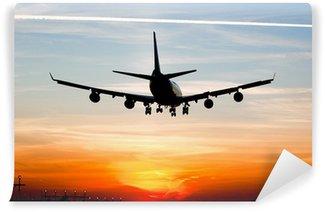 Fototapeta Winylowa Lądowanie samolotu przez sunrise