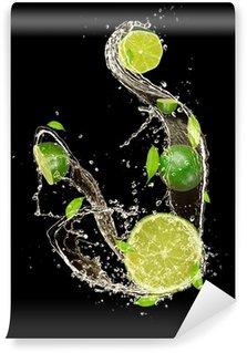 Vinylová Fototapeta Limes ve stříkající vodě, izolovaných na černém pozadí