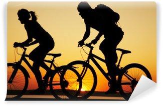 Vinylová Fototapeta Mladý pár jízdě kola při západu slunce