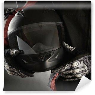 Vinylová Fototapeta Motocyklista s helmou v ruce. Tmavé pozadí