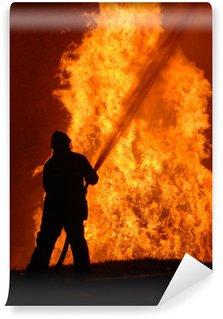 Vinylová Fototapeta Osamělý hasič bojuje proti zuřícího požáru