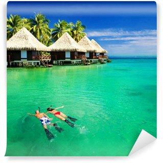 Vinylová Fototapeta Pár šnorchlování v laguně s více než vodní bungalovy