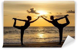 Fototapeta Vinylowa Para robi ćwiczenia jogi razem rozciąganie podczas słońca