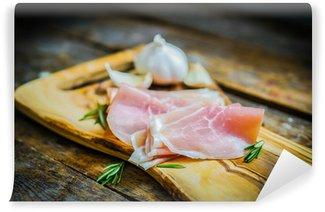Vinylová Fototapeta Prosciutto s česnekem a rozmarýnem na rustikální dřevěné pozadí