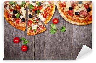 Fototapeta Winylowa Pyszne włoskie pizze podawane na drewnianym stole