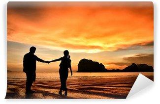 Vinylová Fototapeta Romantický pár se drží za ruce při západu slunce na pláži