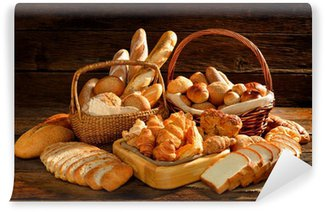 Fototapeta Winylowa Różnorodność chleba w wiklinowym koszu na starym drewnianym tle.