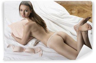 Vinylová Fototapeta Sexy nahá dívka ležící na bílé posteli s polštářem v náručí