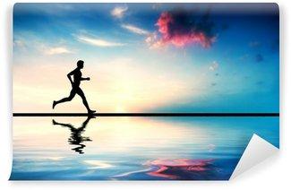 Vinylová Fototapeta Silueta muže běží při západu slunce. Vodní odraz