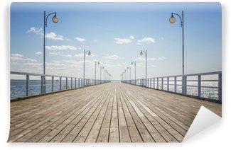 Fototapeta Winylowa Stare drewniane molo na pusty brzeg morza z miejsca na kopię