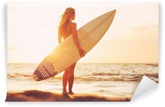 Fototapeta Winylowa Surfer dziewczyna na plaży o zachodzie słońca