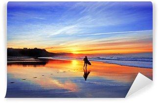 Fototapeta Vinylowa Surfer w plaży o zachodzie słońca