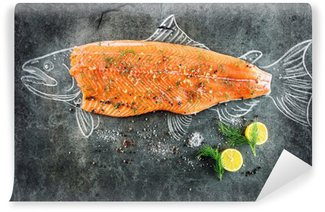 Fototapeta Vinylowa Surowe ryby łososia stek z dodatkami takimi jak cytryny, pieprz, sól morska i koperkiem na czarnej tablicy, naszkicowany obraz kredą łososia stek z ryby