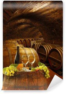 Vinylová Fototapeta Vinný sklípek s sklenky bílého vína proti sudy