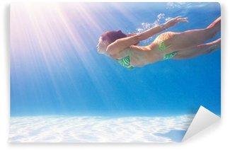 Vinylová Fototapeta Žena plavání pod vodou na modrém bazénu.