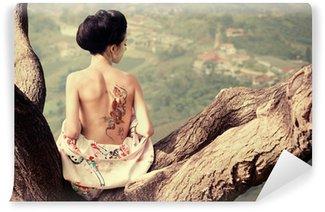 Vinylová Fototapeta Žena s hadem tetování sedí na větvi stromu