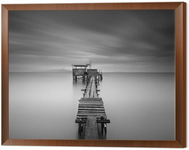 Framed Canvas Fine art image of wooden fishing jetty at beach in black and white.Long exposure shot with motion blur.