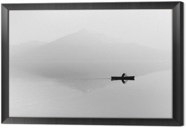 Framed Canvas Fog over the lake. Silhouette of mountains in the background. The man floats in a boat with a paddle. Black and white