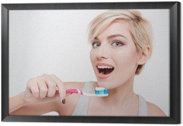 Happy cute woman brushing teeth Framed Canvas