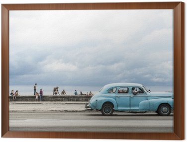 Framed Canvas HAVANA, CUBA - MAY 18, 2011: Classic vintage American car serving as taxi drives along the seafront Malecon, a popular place for socializing in Central Havana.