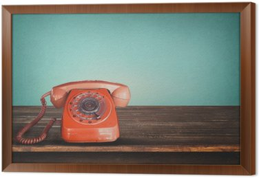 Old retro red telephone on table with vintage green pastel background Framed Canvas