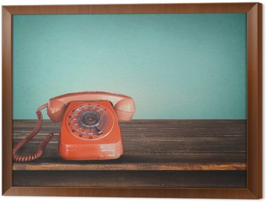Framed Canvas Old retro red telephone on table with vintage green pastel background