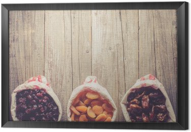 Overhead shot of dried fruits in paper bag on wooden table Framed Canvas