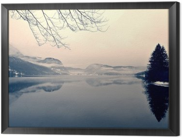Framed Canvas Snowy winter landscape on the lake in black and white. Monochrome image filtered in retro, vintage style with soft focus, red filter and some noise; nostalgic concept of winter. Lake Bohinj, Slovenia.