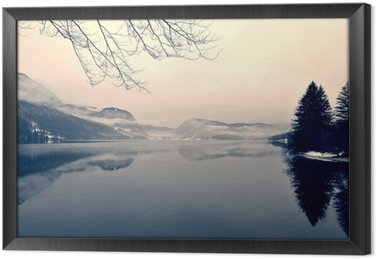 Snowy winter landscape on the lake in black and white. Monochrome image filtered in retro, vintage style with soft focus, red filter and some noise; nostalgic concept of winter. Lake Bohinj, Slovenia. Framed Canvas