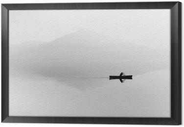 Gerahmtes Leinwandbild Nebel über dem See. Silhouette der Berge im Hintergrund. Der Mann schwimmt in einem Boot mit einem Paddel. Schwarz und weiß