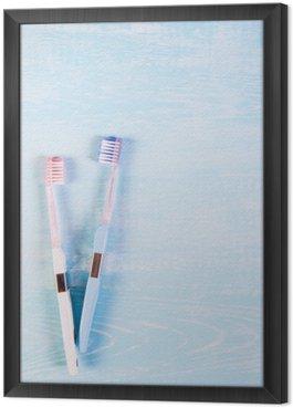 Gerahmtes Leinwandbild Zwei Zahnbürsten und Kamillenblüten auf einem hellen Hintergrund. Das Konzept der Naturkosmetik für die Gesundheit. Du mich. Blick von oben