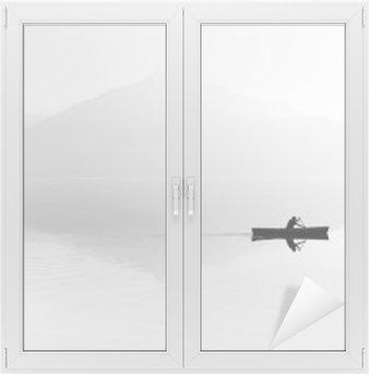 Glas- och Fönsterdekorer Dimma över sjön. Siluett av bergen i bakgrunden. Mannen flyter i en båt med en paddel. Svartvitt