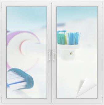 Glas- och Fönsterdekorer Elektriska och klassisk tandborste på reflekterande yta och ljusblå bakgrund.