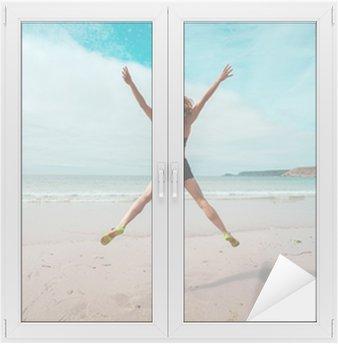 Nuori nainen tekee tähti hyppää rannalla Ikkuna- Ja Lasitarra