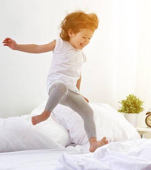 Glad barnflicka hoppar och spelar