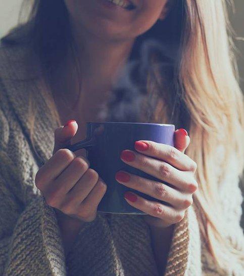Händer som håller varm kopp kaffe eller te på morgonen